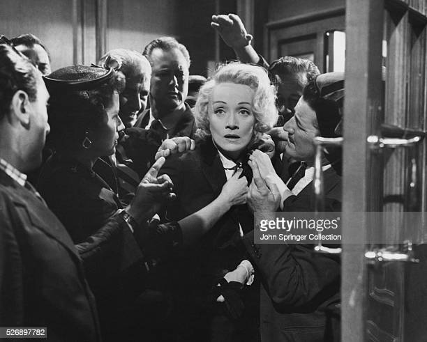 A drained Christine Helm Vole is surrounded by reporters in Witness for the Prosecution