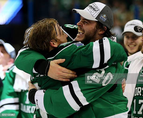Drake Caggiula and Gage Ausmus of the North Dakota Fighting Hawks celebrate the win over the Quinnipiac Bobcats after the championship game of the...