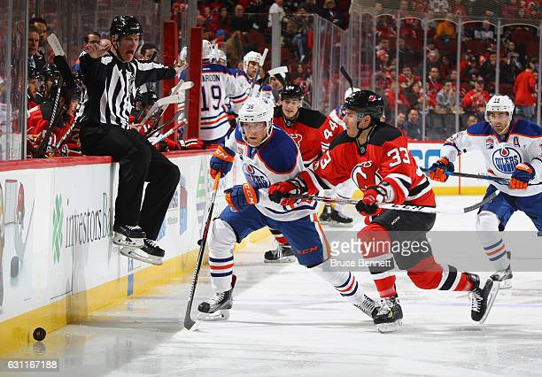 Drake Caggiula of the Edmonton Oilers and Yohann Auvitu of the New Jersey Devils pursue the puck during the first period at the Prudential Center on...
