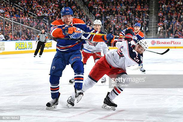 Drake Caggiula of the Edmonton Oilers battles for the puck against Markus Nutivaara of the Columbus Blue Jackets on December 13 2016 at Rogers Place...