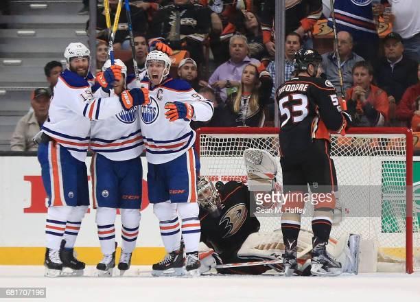 Drake Caggiula of the Edmonton Oilers celebrates scoring a goal against goaltender John Gibson and Shea Theodore of the Anaheim Ducks with Patrick...