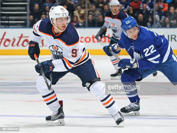 Drake Caggiula of the Edmonton Oilers looks for a lead pass in front of Nikita Zaitsev of the Toronto Maple Leafs during an NHL game at the Air...