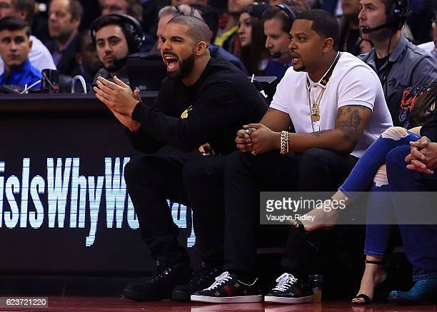 Drake cheers from his courtside seat during the first half of an NBA game between the Golden State Warriors and the Toronto Raptors at Air Canada...