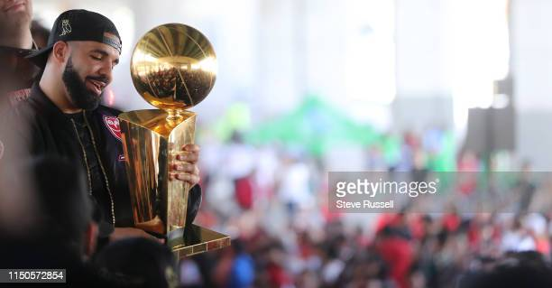 Drake holds the Larry O'Brien NBA Championship Trophy as the Toronto Raptors hold their victory parade after beating the Golden State Warriors in the...