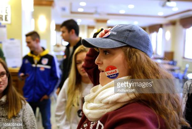 Drake University student Camryn Kubicki applies a sticker to her hat after voting at a polling station on November 6 2018 in Des Moines Iowa Today's...