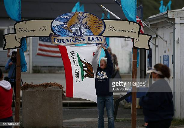 Drakes Bay Oyster Co worker Andrea Perone hangs the California state flag from a sign on the final day of retail and canning operations at the Drakes...