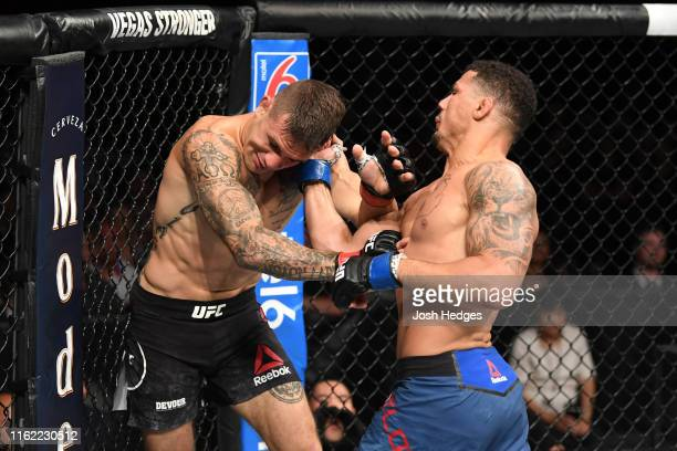 Drakkar Klose punches Christos Giagos in their lightweight bout during the UFC 241 event at the Honda Center on August 17, 2019 in Anaheim,...