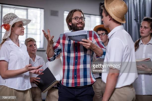 Drama teacher eading students wearing props