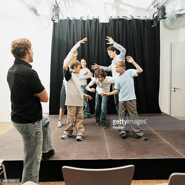 Drama Teacher Watches Schoolchildren Acting on Stage