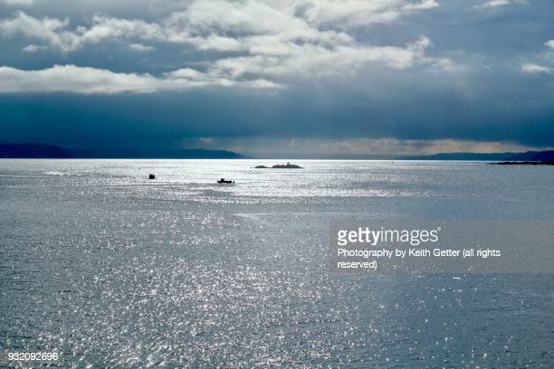 A dramatic and expansive sky with clouds, rain and sunlight shining on the Puget Sound  in the Pacific Northwest USA