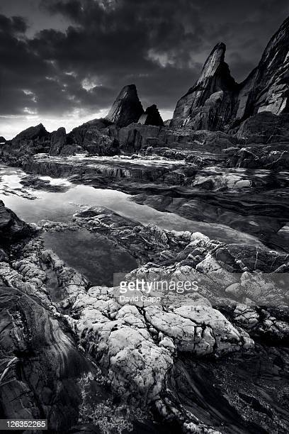 a dramatic black and white view of a sunset over the rugged rock formations at westcombe bay in devon. - seascape stock pictures, royalty-free photos & images