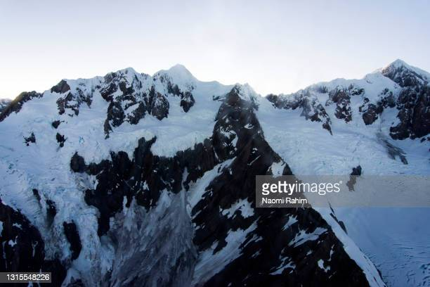 dramatic close up aerial view of franz josef glacier peak, new zealand - 2017 stock pictures, royalty-free photos & images