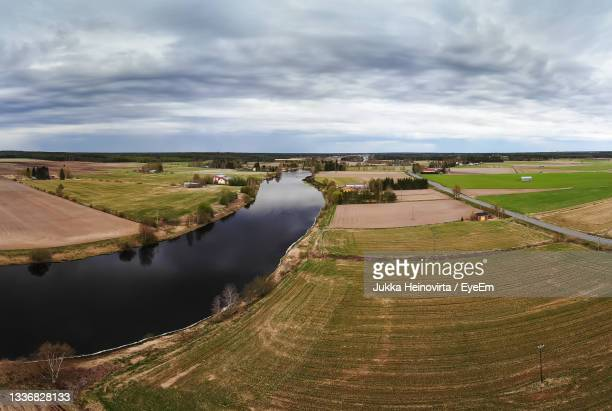 a dramatic cloud formation over the river and fields at the rural finland. - heinovirta stock pictures, royalty-free photos & images
