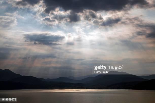 Dramatic cloud formation, sunbeams behind dark clouds, thunderstorm atmosphere, Lago Maggiore, Verbano-Cusio-Ossola province, Piedmont region, Italy