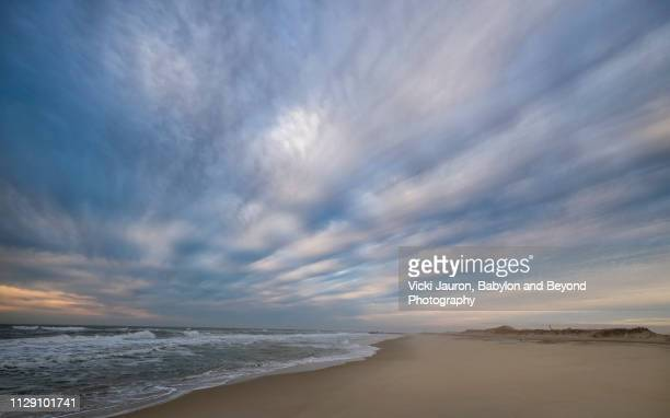 dramatic cloud lines against the water at jones beach, long island - jones beach stock pictures, royalty-free photos & images