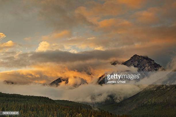 dramatic clouds at sunset covering mountain top