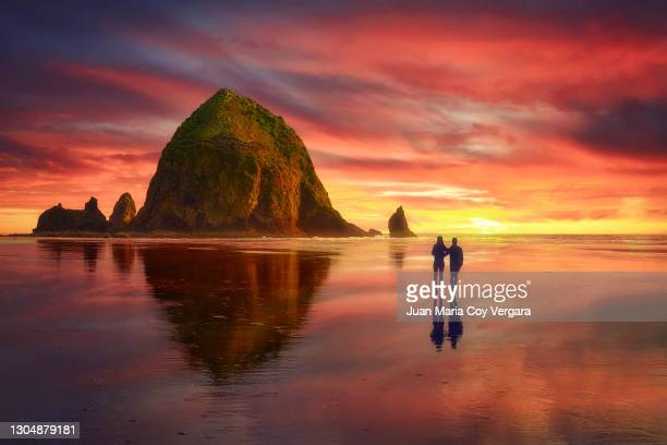 dramatic clouds caressing haystack rock at sunset - cannon beach (oregon, usa) - 放浪願望 ストックフォトと画像
