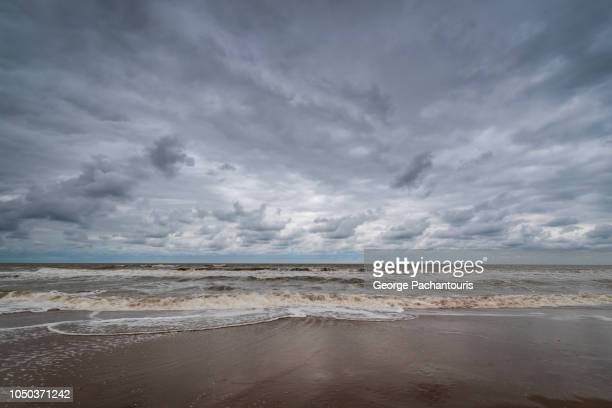 dramatic clouds on a beach - overcast stock pictures, royalty-free photos & images