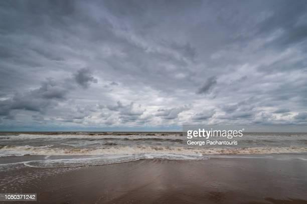 dramatic clouds on a beach - bewolkt stockfoto's en -beelden