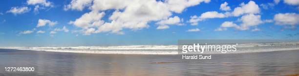 dramatic clouds over the pacific ocean with waves, shoreline and sandy beach along the oregon coastline. - manzanita stock pictures, royalty-free photos & images