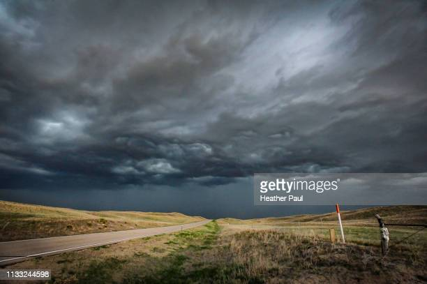 dramatic dark storm clouds over rural country road - moody sky stock pictures, royalty-free photos & images