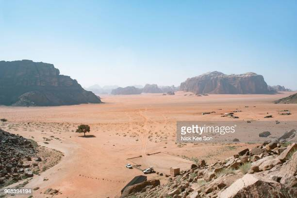 dramatic desert wilderness of sandstone and granite as seen from lawrence spring, wadi rum, jordan - heat haze stock pictures, royalty-free photos & images