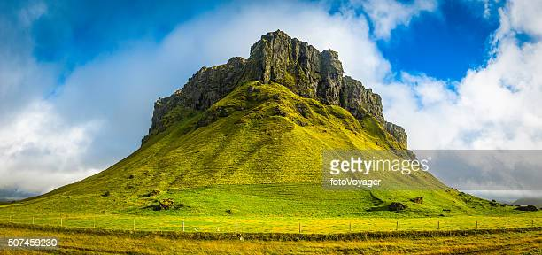 Dramatic green mountain grassy pasture rocky peaks panorama Iceland