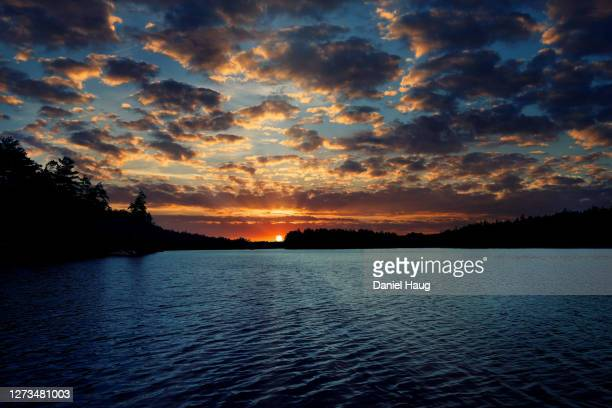 dramatic high contrast late summer sunset over a quiet northern lake in cottage country - lake sunset stock pictures, royalty-free photos & images