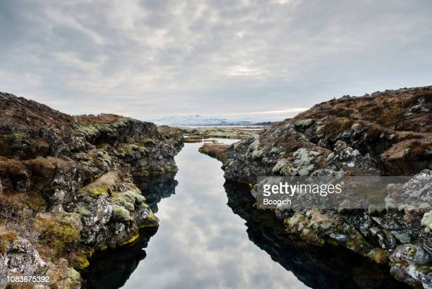 dramatic iceland landscape of the silfra fissure thingvellir national park iceland - thingvellir stock photos and pictures