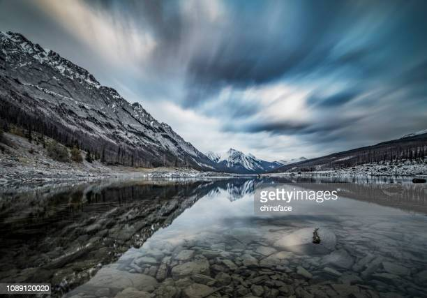 dramatic landscape of medicine lake with rocky mountains - dramatic landscape stock pictures, royalty-free photos & images