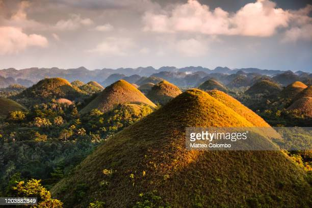 dramatic light over chocolate hills, bohol, philippines - paisajes de filipinas fotografías e imágenes de stock