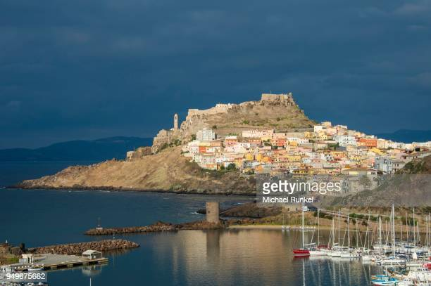 Dramatic light over the old town of Castelsardo with its boat harbour, Sardinia, Italy