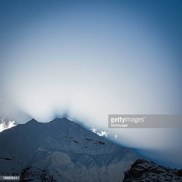 Dramatic light rays over snow capped mountain peaks
