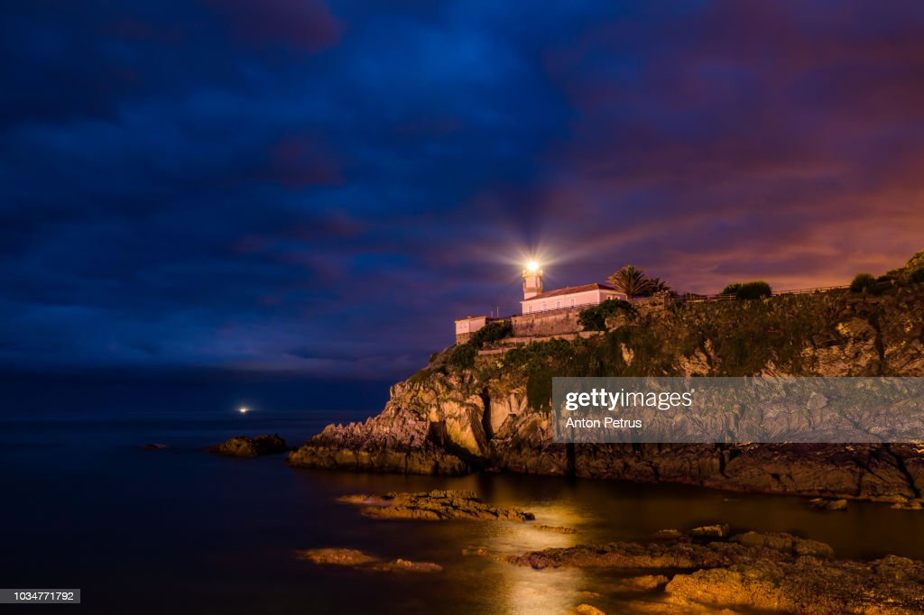 Dramatic night landscape with lighthouse, Cudillero, Spain : Stock Photo