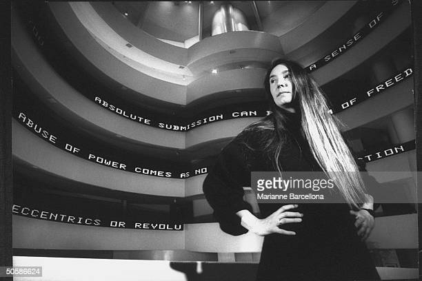 Dramatic of artist Jenny Holzer standing in front of her installation at Guggenheim Museum