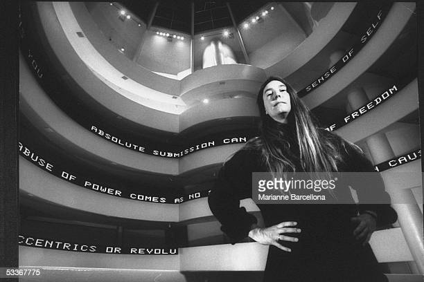 Dramatic of artist Jenny Holzer standing in front of her installation at the Guggenheim Museum