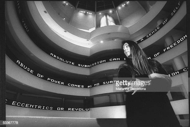 Dramatic of artist Jenny Holzer standing in front of her installation looking sideways at the Guggenheim Museum