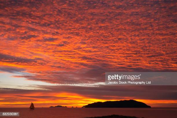 dramatic orange clouds in sunset sky - whangarei heads stock-fotos und bilder