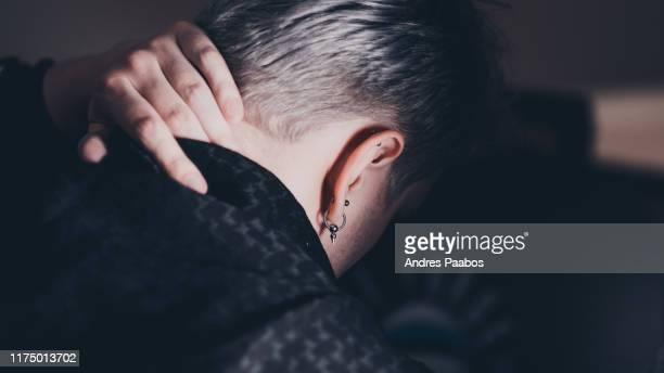 dramatic photo of man with piercings, contemplating - イヤリング ストックフォトと画像