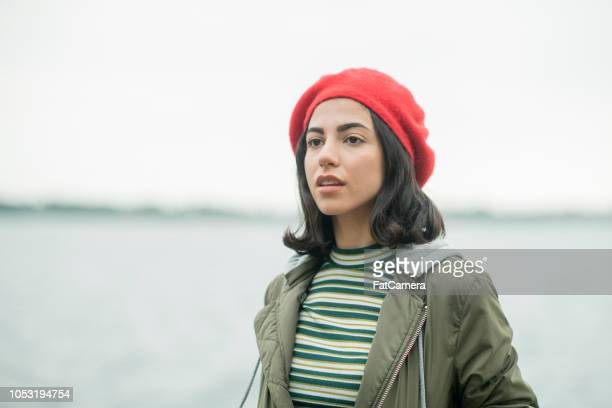 dramatic portrait of a young black-haired woman wearing a beret by the water - giudaismo foto e immagini stock