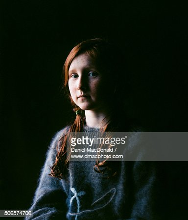 Dramatic portrait of young redheaded girl in soft window light with black background