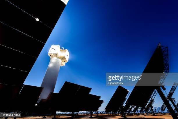 dramatic rays from solar energy generation plant in south african desert - africa stock pictures, royalty-free photos & images