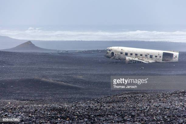Dramatic scene of abandoned plane wreck on black beach in Iceland