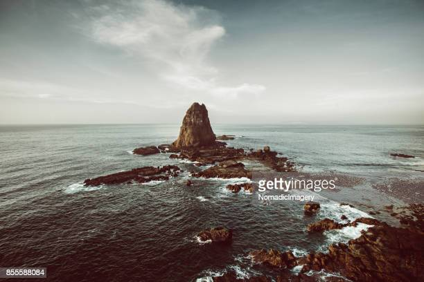 Dramatic seascape of Papuma rock outcrop in the Java sea