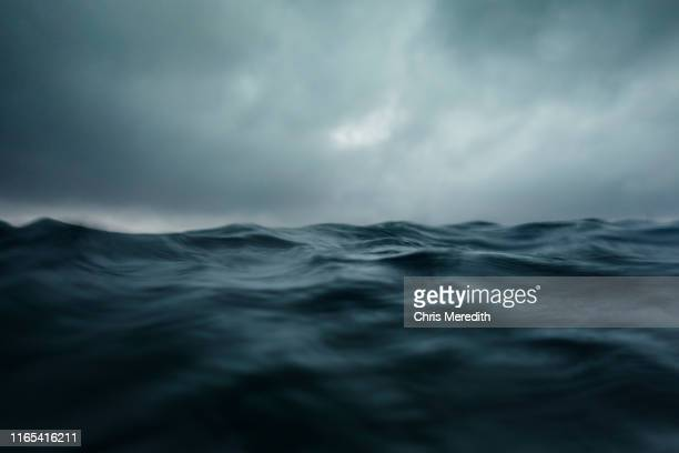 dramatic seascape with ocean wave and dark sky - meer stock-fotos und bilder