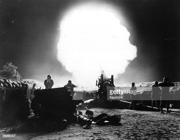 Dramatic shot of 155mm Howitzer fire during night action in the Korean War.