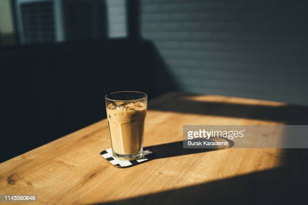 dramatic shot of ice coffee at sunset with shadow - koffie drank stockfoto's en -beelden