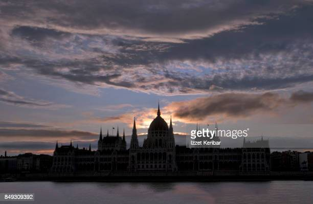 dramatic skies and silhouetted photo of the parliament building at budapest, hungary - hungary stock pictures, royalty-free photos & images
