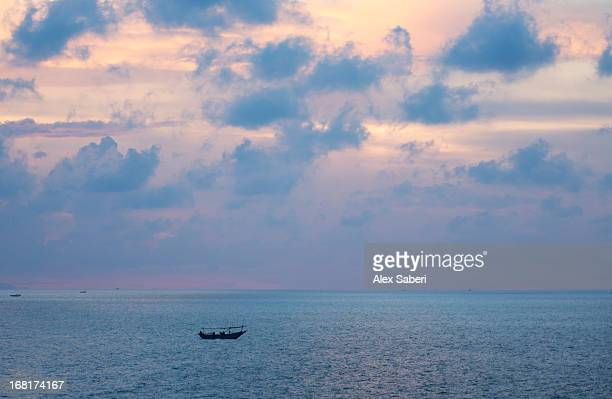 a dramatic sky above a fishing boat off the central java coast. - alex saberi stock pictures, royalty-free photos & images