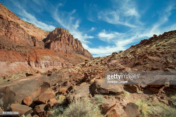 Dramatic sky and cloud landscape over remote red rock desert canyon walls.